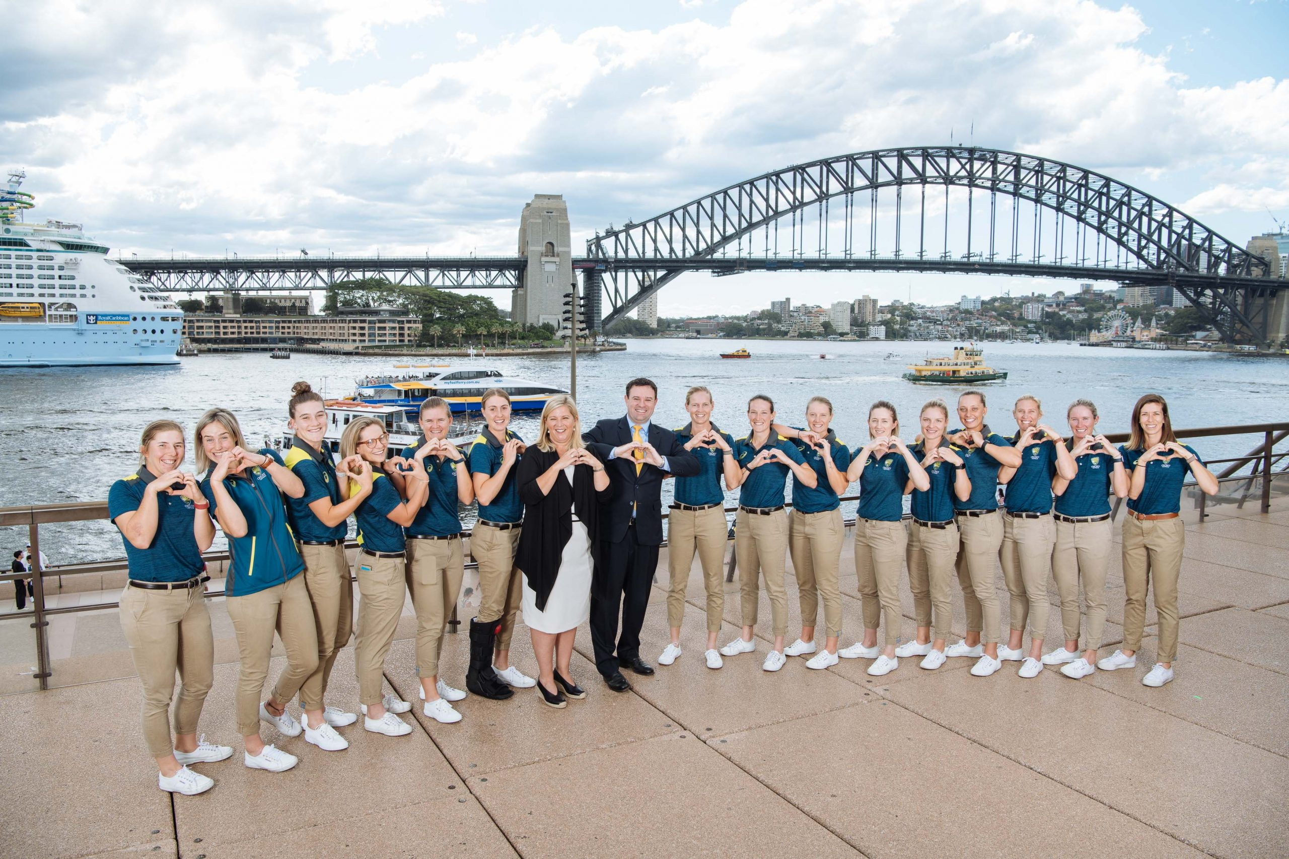 Photo of the Australian Women's Cricket Team and Ministers Taylor and Ayres in the Opera House forecourt, with the Harbour Bridge in the background. They are doing the Love NSW hand shape